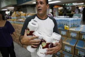 A man carries toilet paper at a supermarket in Caracas